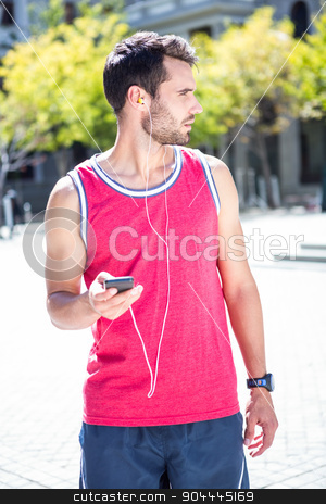 Handsome athlete sending a text stock photo, Handsome athlete sending a text while looking away on a sunny day by Wavebreak Media