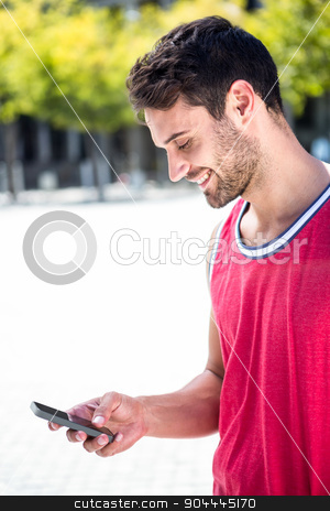 Smiling handsome athlete sending a text stock photo, Smiling handsome athlete sending a text on a sunny day by Wavebreak Media