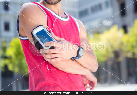 Handsome athlete adjusting his armband stock photo, Profile view of an handsome athlete adjusting his armband on a sunny day by Wavebreak Media