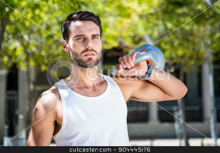 Handsome athlete outfit with a kettlebell stock photo, Handsome athlete outfit with a kettlebell on a sunny day by Wavebreak Media