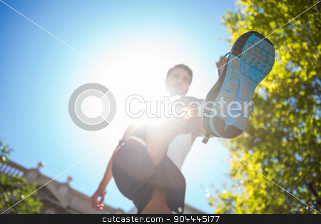 Handsome athlete running in the street stock photo, Low angle view of an athlete running in the street on a sunny day by Wavebreak Media