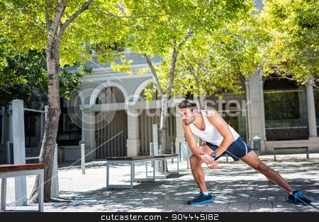 Handsome athlete stretching his leg stock photo, Handsome athlete stretching his leg in the city by Wavebreak Media
