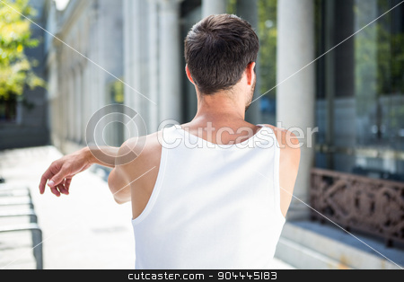 Rear view of athlete stretching his arm stock photo, Rear view of athlete stretching his arm in the city by Wavebreak Media