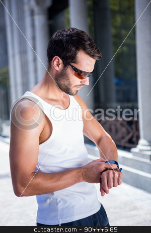 Handsome athlete with sunglasses setting heart rate watch stock photo, Handsome athlete with sunglasses setting heart rate watch in the city by Wavebreak Media