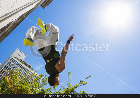 Extreme athlete jumping in the air in front of a building stock photo, Extreme athlete jumping in the air in front of a building in the city by Wavebreak Media
