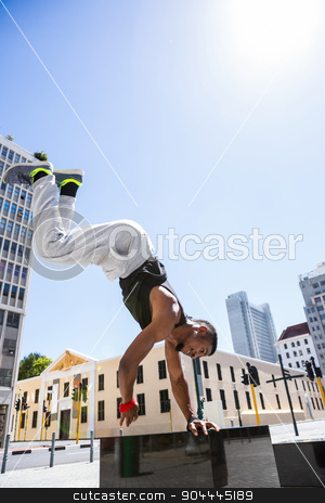 Handsome athlete doing a headstand stock photo, Handsome athlete doing a headstand on a sunny day by Wavebreak Media