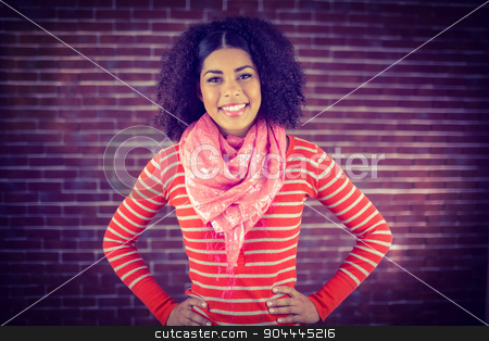 Smiling attractive woman with hands on hips stock photo, Portrait of smiling attractive woman with hands on hips against red brick background by Wavebreak Media