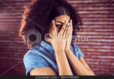 Attractive young woman hiding behind hands stock photo, Portrait of attractive young woman hiding behind hands against red brick background by Wavebreak Media