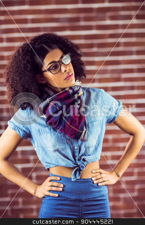 Attractive hipster posing with hands on hips stock photo, Attractive hipster posing with hands on hips against red brick background by Wavebreak Media