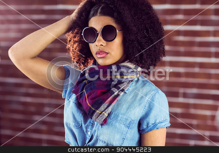 Attractive young woman wearing sunglasses stock photo, Attractive young woman wearing sunglasses against red brick background by Wavebreak Media
