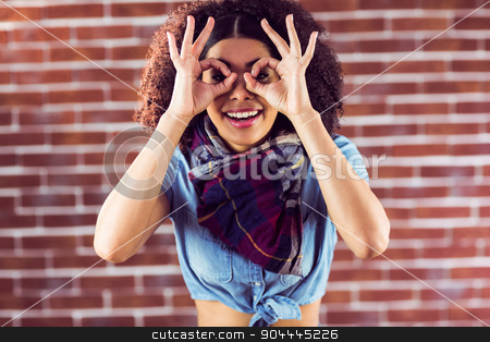 Smiling attractive young woman having fun stock photo, Portrait of smiling attractive young woman having fun against red brick background by Wavebreak Media