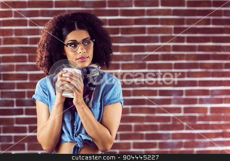 Attractive hipster holding take-away cup stock photo, Attractive hipster holding take-away cup against red brick background by Wavebreak Media