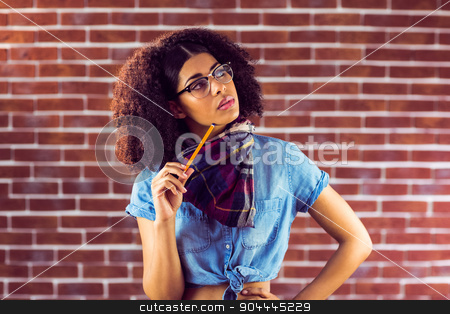 Daydreaming attractive hipster holding pen stock photo, Daydreaming attractive hipster holding pen against red brick background by Wavebreak Media