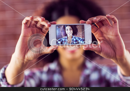 Attractive young woman taking selfies with smartphone stock photo, Attractive young woman taking selfies with smartphone against red brick background by Wavebreak Media