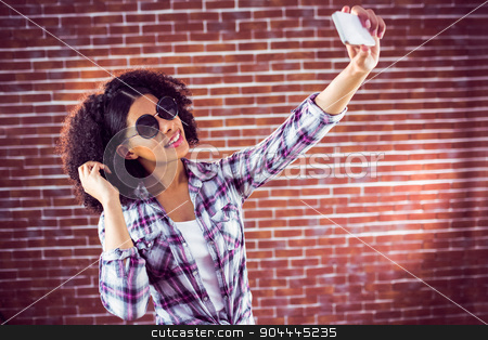 Attractive hipster taking selfies with smartphone stock photo, Attractive hipster taking selfies with smartphone against red brick background by Wavebreak Media