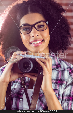 Attractive smiling hipster holding camera stock photo, Portrait of attractive smiling hipster holding camera against red brick background by Wavebreak Media