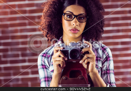 Attractive focused hipster photographing  stock photo, Portrait of attractive focused hipster photographing against red brick background by Wavebreak Media
