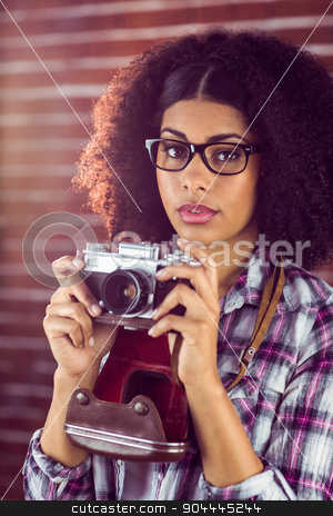Attractive hipster photographing with camera stock photo, Portrait of attractive hipster photographing with camera against red brick background by Wavebreak Media