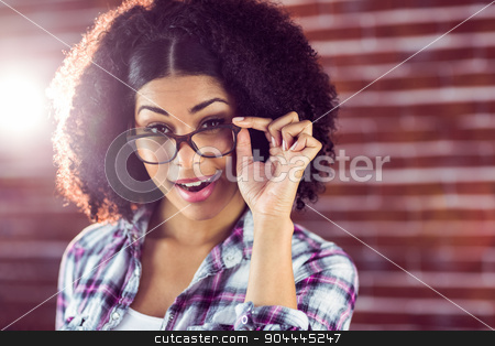 Attractive hipster posing with glasses stock photo, Portrait of attractive hipster posing with glasses against red brick background by Wavebreak Media