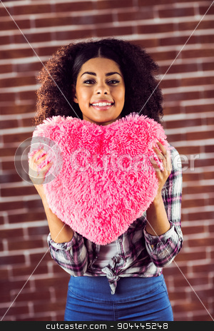 Attractive young woman holding up heart-shaped pillow stock photo, Portrait of attractive young woman holding up heart-shaped pillow against red brick background by Wavebreak Media