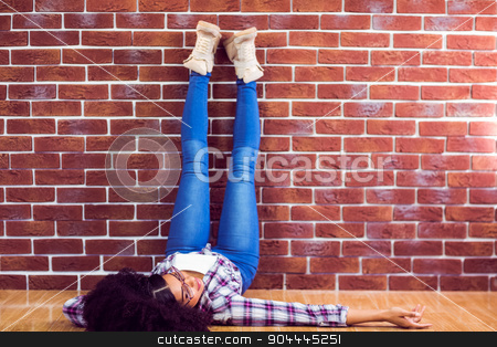 Attractive hipster lying on ground and holding legs up  stock photo, Attractive hipster lying on ground and holding legs up against red brick background by Wavebreak Media