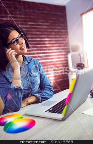 Casual businesswoman calling a client stock photo, Casual businesswoman calling a client at the office by Wavebreak Media