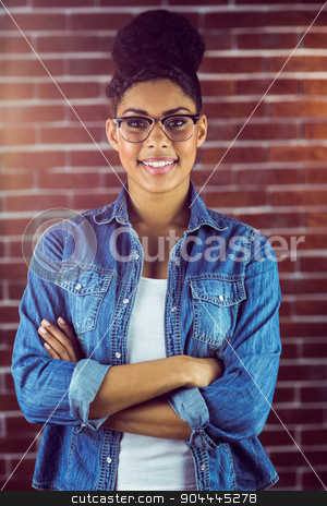 Gorgeous hipster with arm crossed posing with glasses stock photo, Portrait of a gorgeous hipster posing with glasses against red brick background by Wavebreak Media