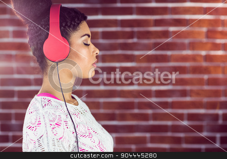 A beautiful woman concentrated on her music stock photo, A beautiful woman concentrated on her music on a brick wall by Wavebreak Media