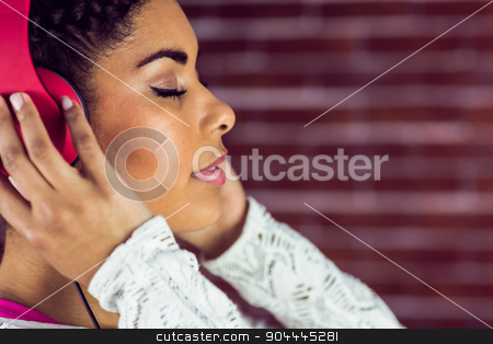 Young woman enjoying her music stock photo, Young woman enjoying her music against a brick wall by Wavebreak Media