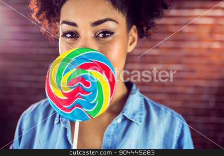 A beautiful woman holding a giant lollipop  stock photo, A beautiful woman holding a giant lollipop against a red brick wall by Wavebreak Media