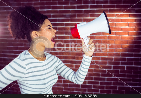 Young woman using her megaphone in the light  stock photo, Young woman using her megaphone in the light against a red brick wall by Wavebreak Media