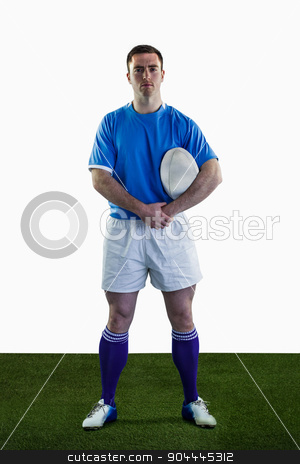 Rugby player holding a rugby ball stock photo, Portrait of a standing rugby player holding a rugby ball by Wavebreak Media
