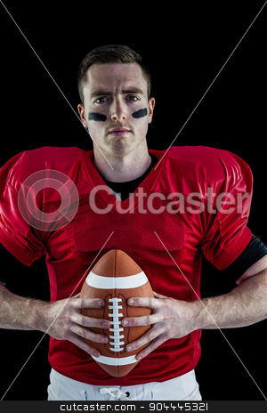 American football player holding a ball stock photo, Portrait of an american football player holding a ball by Wavebreak Media