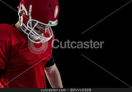 Close up view of american football player focusing stock photo, Close up view of american football player focusing against black background by Wavebreak Media