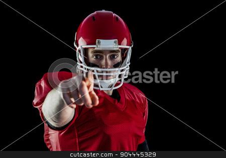Portrait of american football player pointing to camera stock photo, Portrait of american football player pointing to camera against black background by Wavebreak Media