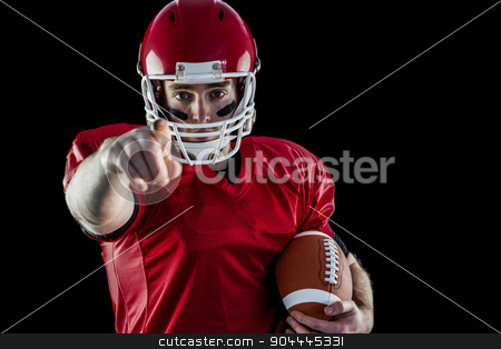 Portrait of american football player holding football and pointi stock photo, Portrait of american football player holding football and pointing to camera against black background by Wavebreak Media