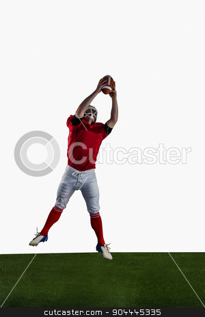 American football player catching football stock photo, American football player catching football on american football field by Wavebreak Media