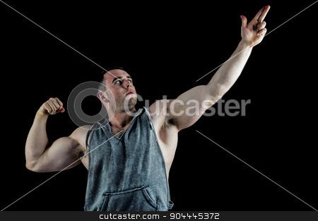 Handsome bodybuilder posing with arms up stock photo, Handsome bodybuilder posing with arms up on black background by Wavebreak Media