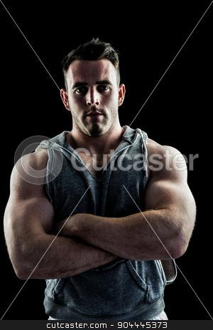 Handsome bodybuilder with arms crossed stock photo, Handsome bodybuilder with arms crossed on black background by Wavebreak Media