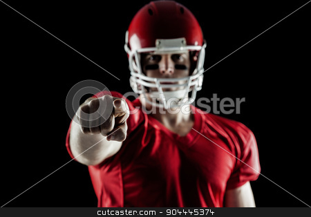 American football player pointing at camera stock photo, American football player pointing at camera on black background by Wavebreak Media