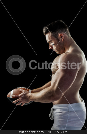 Shirtless American football player with ball stock photo, Shirtless American football player with ball on black background by Wavebreak Media