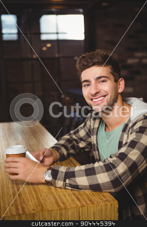 Smiling hipster holding smartphone and take-away cup stock photo, Portrait of smiling hipster holding smartphone and take-away cup at coffee shop by Wavebreak Media