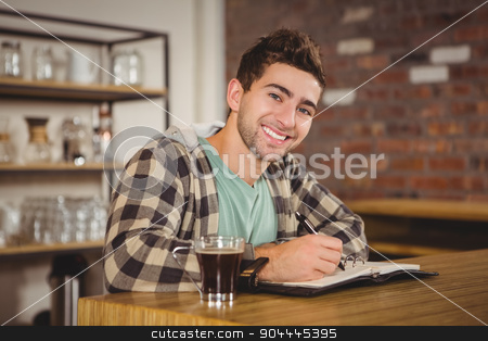 Smiling hipster having coffee and writing in planner stock photo, Portrait of smiling hipster having coffee and writing in planner at coffee shop by Wavebreak Media