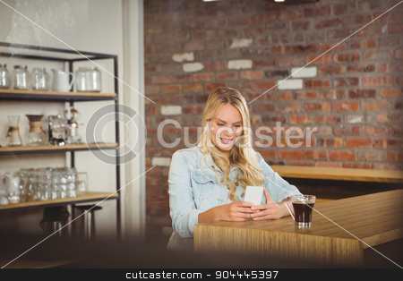 Smiling blonde having coffee and using smartphone stock photo, Smiling blonde having coffee and using smartphone at coffee shop by Wavebreak Media