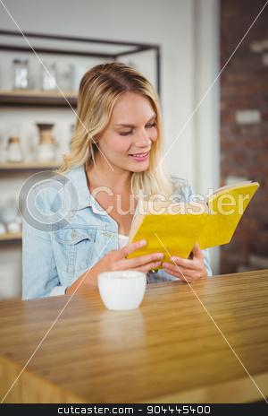 Smiling blonde reading yellow book stock photo, Smiling blonde reading yellow book at coffee shop by Wavebreak Media