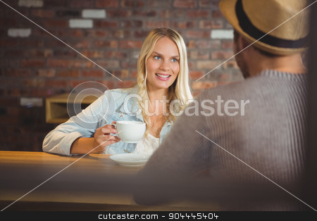 Smiling blonde drinking coffee with friend stock photo, Smiling blonde drinking coffee with friend at coffee shop by Wavebreak Media