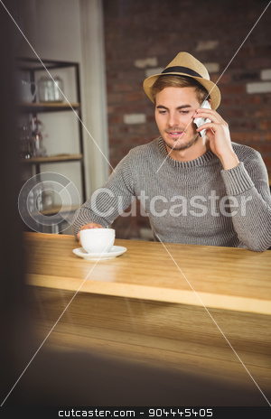 Handsome hipster having coffee and phoning stock photo, Handsome hipster having coffee and phoning at coffee shop by Wavebreak Media