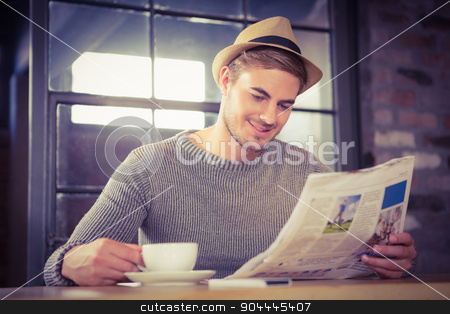 Handsome hipster having coffee and reading newspaper stock photo, Handsome hipster having coffee and reading newspaper at coffee shop by Wavebreak Media