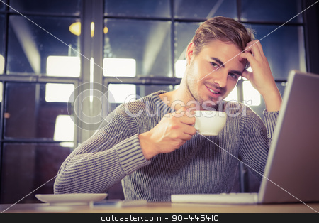 Handsome man smiling and drinking coffee stock photo, Portrait of handsome man smiling and drinking coffee at coffee shop by Wavebreak Media