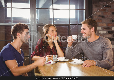 Smiling friends talking and enjoying coffee and cake stock photo, Smiling friends talking and enjoying coffee and cake at coffee shop by Wavebreak Media